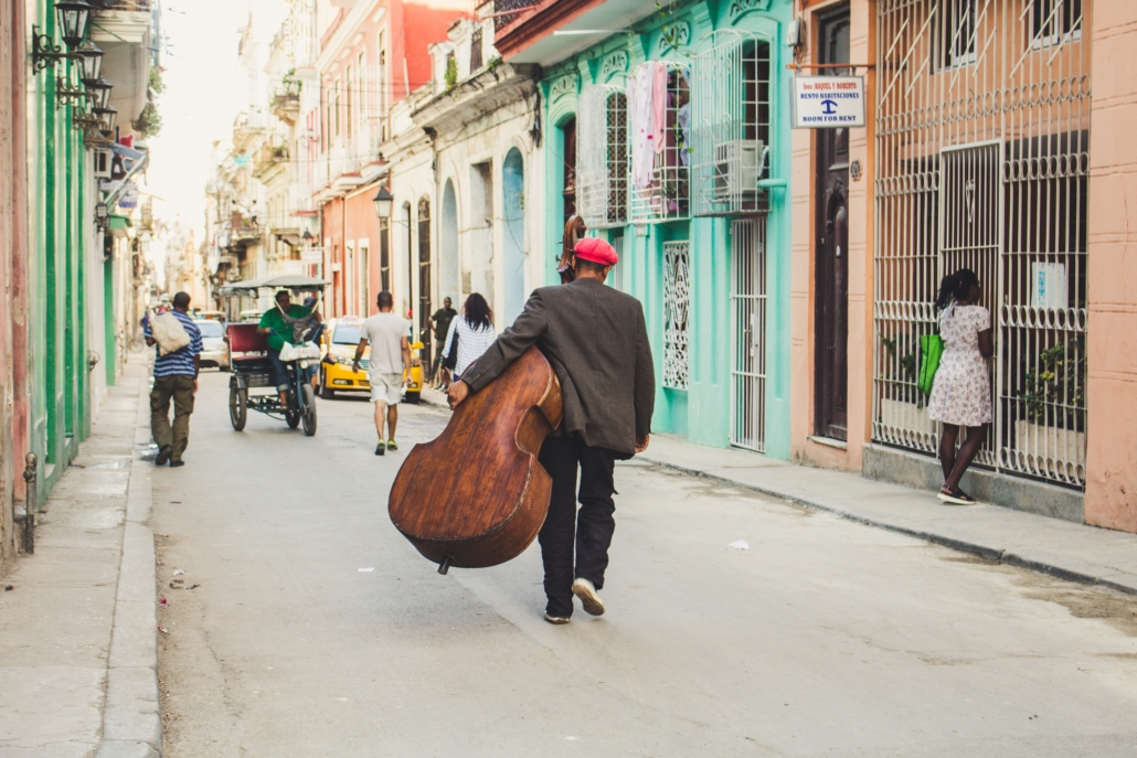 man wondering the streets carrying an instrument