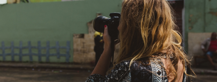 blond woman taking pictures in Havana, Cuba