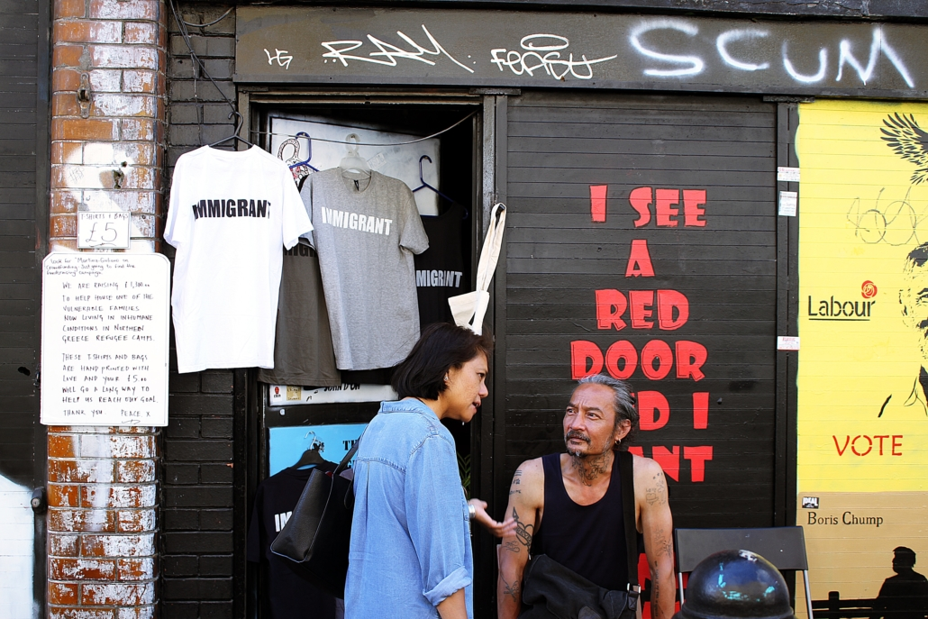 expats in front of a shop, and T-shirts saying Immigrant are for sale