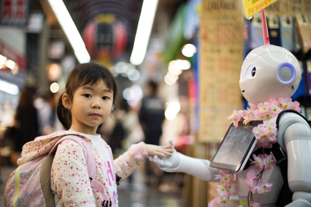 Asian little girl holding hand with a robot her size
