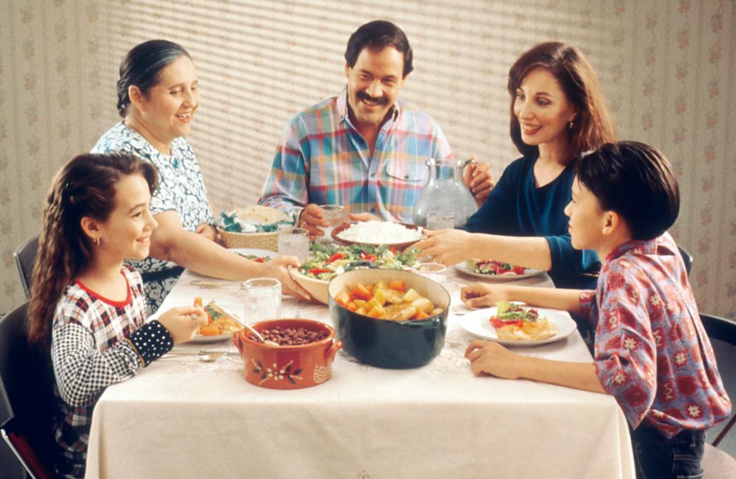 Latino family around dinner table