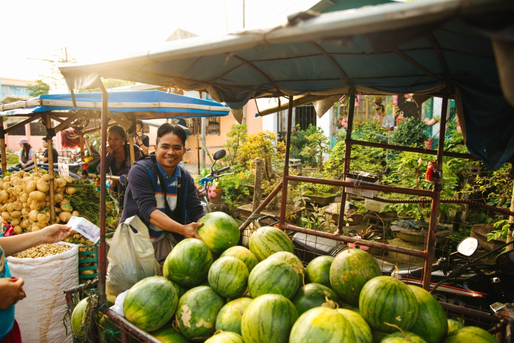 man selling water melons in the market in the philippines